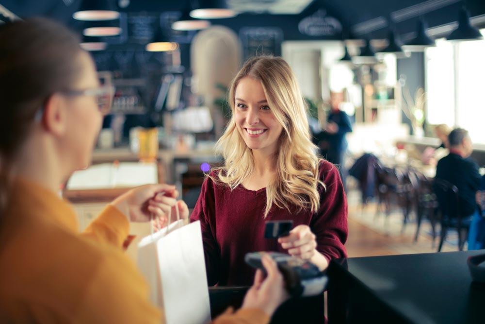 mulher recebendo sacola de compras da vendedora